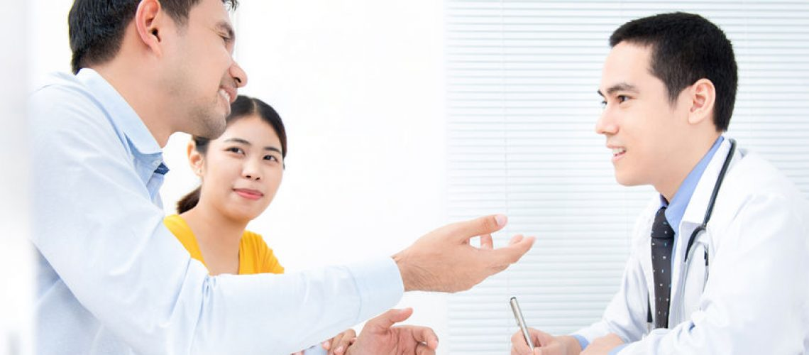 Young Asian couple talking with doctor